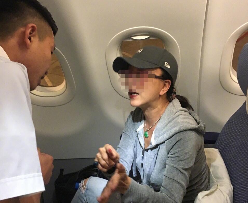 邻座女乘客飞机上玩手机